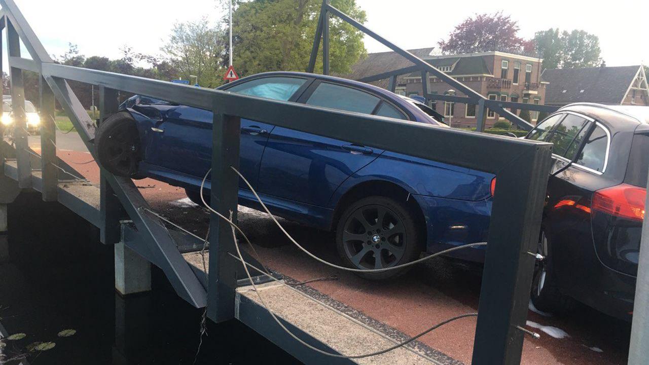 Auto belandt in hekwerk van brug na botsing in Dedemsvaart.