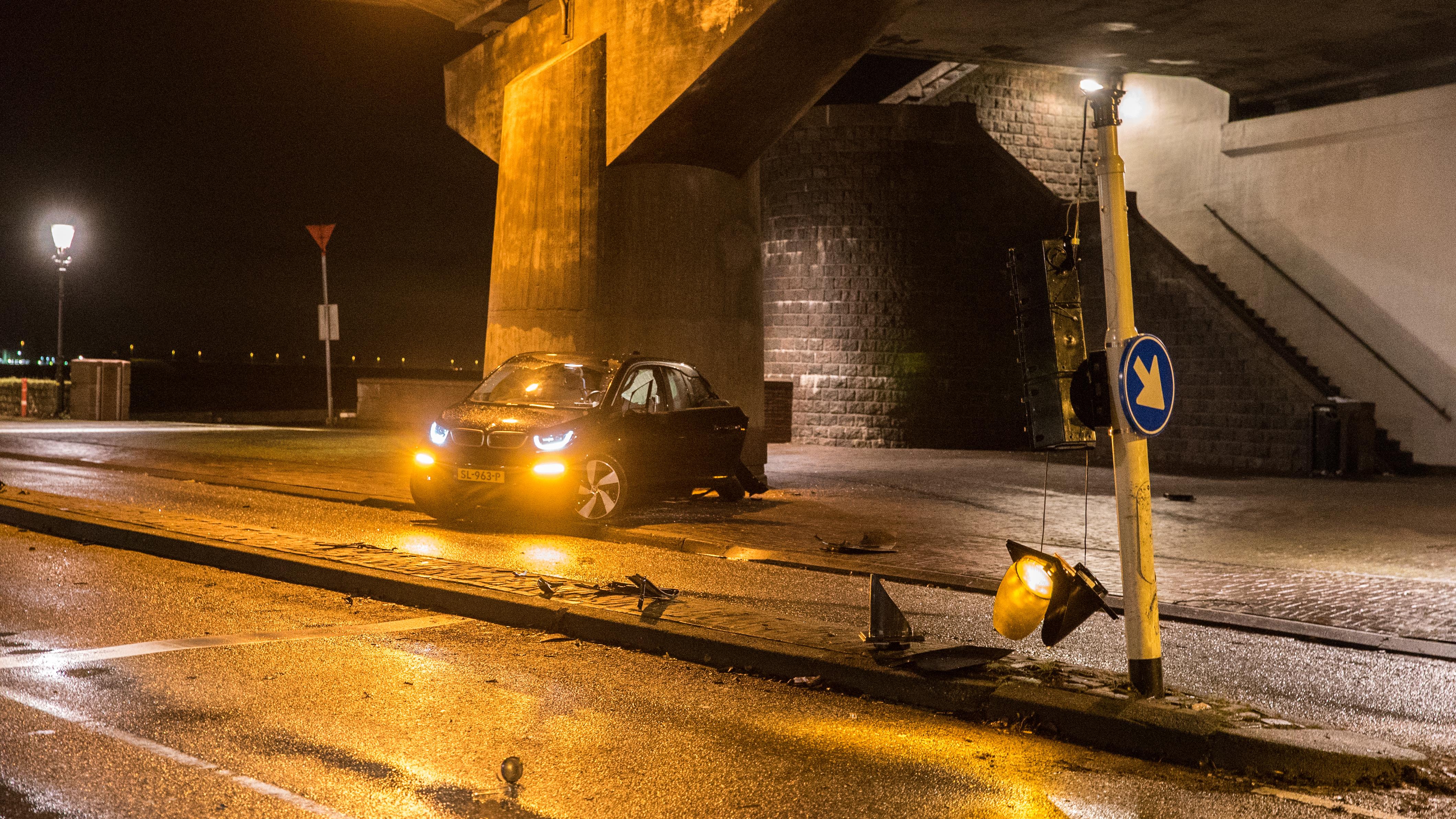 Ravage bij aanrijding personenauto met verkeerslicht en pijler Wilhelminabrug Deventer.