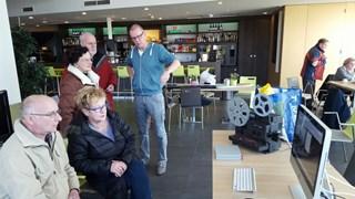 Meneer en mevrouw Veltman bekijken hun video, terwijl Ringeling op de achtergrond uitleg geeft