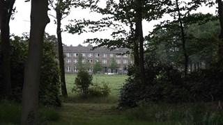 Het azc gezien vanuit de tuin van De Zwanenhof