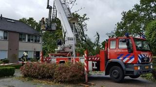 Brandweer haalt eik van dak wning