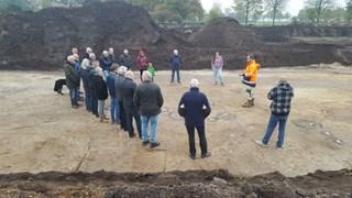 Belangstellenden bekijken de opgravingen