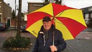 Go Ahead Eagles-supporter Willem de Witte: schuilen onder rood-gele paraplu