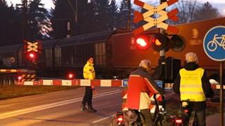Een agent regelt het verkeer bij een overweg