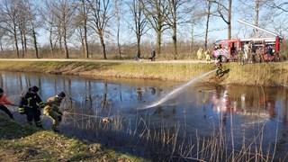 Brandweerlieden moeten vanaf beide waterkanten in actie komen om de eend te kunnen bevrijden