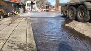 Straat onder water na waterleidingbreuk