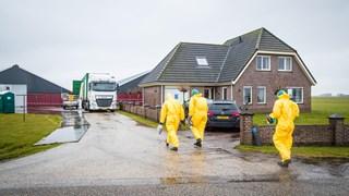 Mannen in gele pakken lopen naar het besmette bedrijf in Kamperveen