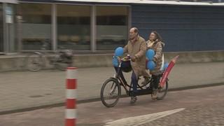 In Hengelo brengt burgemeester Schelberg stemmers op een tandem naar het stemlokaal