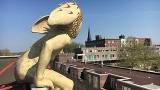 Muziekgod Pan kijkt uit over Enschede vanaf het dak van het conservatorium