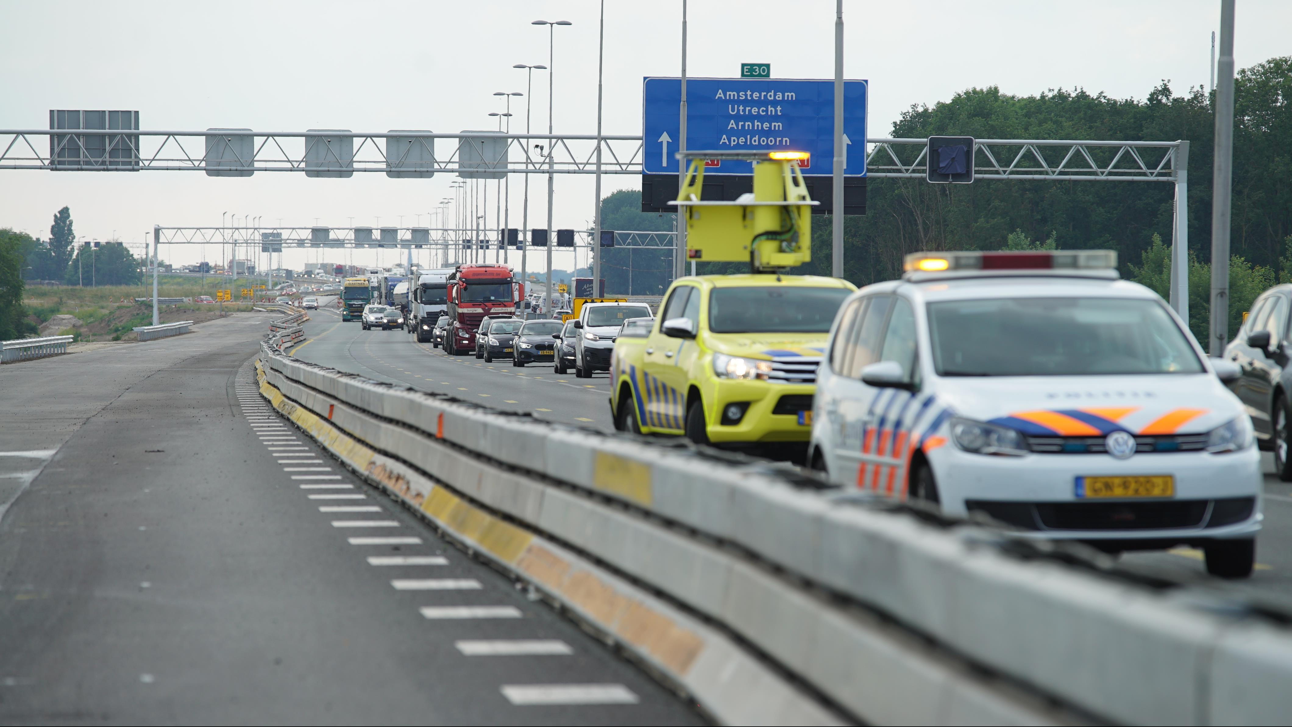 Flinke vertraging op A1 bij Deventer door ongeluk met auto en twee vrachtwagens.